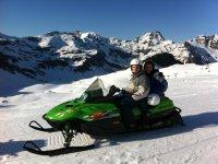 Moto de nieve con las montanas de fondo