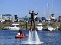 chico practicando flyboard mientras el monitor esta de pie en su moto de agua
