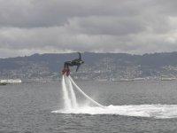 realizando una acrobacia en el aire mientras practica flyboard