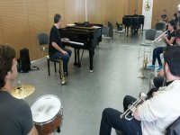 man next to a piano and students sitting in their chairs with wind instruments