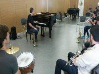 hombre junto a un piano y alumnos sentados en sus sillas con instrumentos de viento