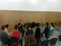 teacher playing wind instrument with students around