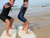 Alumna y monitor sobre las tablas de surf