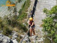 bambino che pratica arrampicata con il fiume sullo sfondo