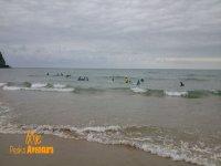persone che navigano su una spiaggia con onde