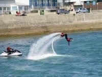 hombre practicando acrobacia lateral con una moto de agua blanca al lado