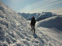 hombre caminando por una montana de nieve