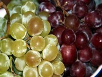 two clusters of green and reddish grapes