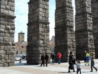 people walking under the aqueduct of segovia