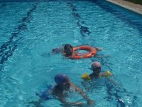 Children bathing in a pool with sleeves and float.JPG