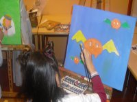nina painting bats on a blue background