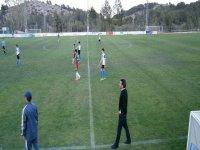ninos jugando al futbool con los entrenadores en el cesped