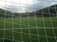 View of a football field from behind the net of a goal post