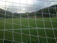 vista de un campo de futbol desde detras de la red de una porteria