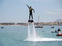 chica con postura de acrobata mientras practica flyboard
