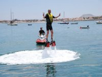 Uomo felice in aria mentre si pratica il flyboard