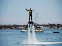 Giovane uomo che tiene equlibrio mentre si pratica il flyboard