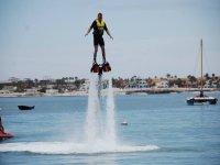 chico con chaleco amarillo volando en el aire con dos chorros de agua bajo sus pies