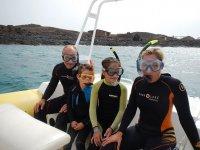 familia con trajes de neopreno y gafas de buceo a punto de practicar snorkel