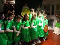 ninos con unas bolsas verdes haciendo una actuacion