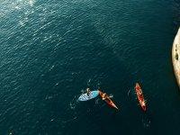 Kayaks and SUP board sailing together