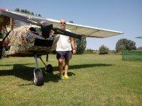 Junto a la avioneta en la pista de aterrizaje
