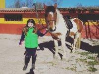 Alumna de equitación junto al caballo