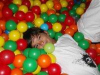 Tumbado sobre las pelotas de colores