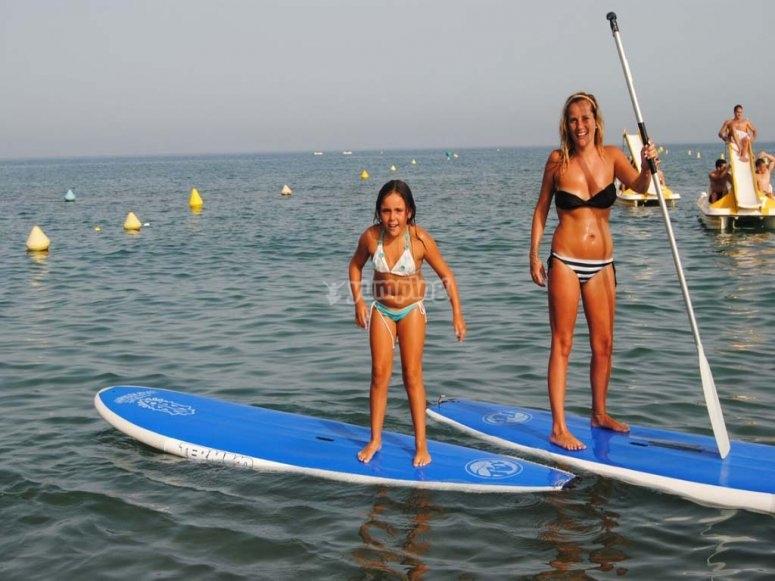 Madre e hija practicando paddle surf