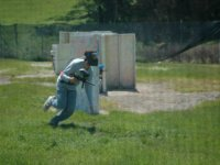 chico corriendo en un campo de paintball