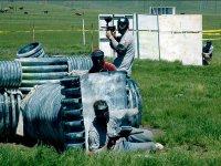 tres chicos jugando al paintball escondidos detras de unos elementos