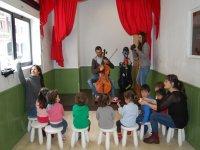 un hombre tocando el violonchelo mientras unos ninos le miran