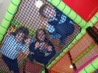 tres ninos en un parque infantil detras de unas cuerdas