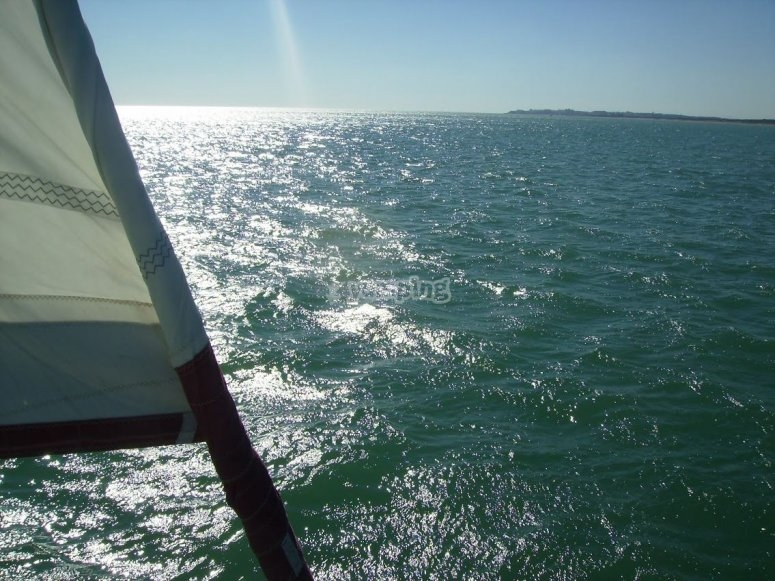 Vela y rayo de sol sobre el mar