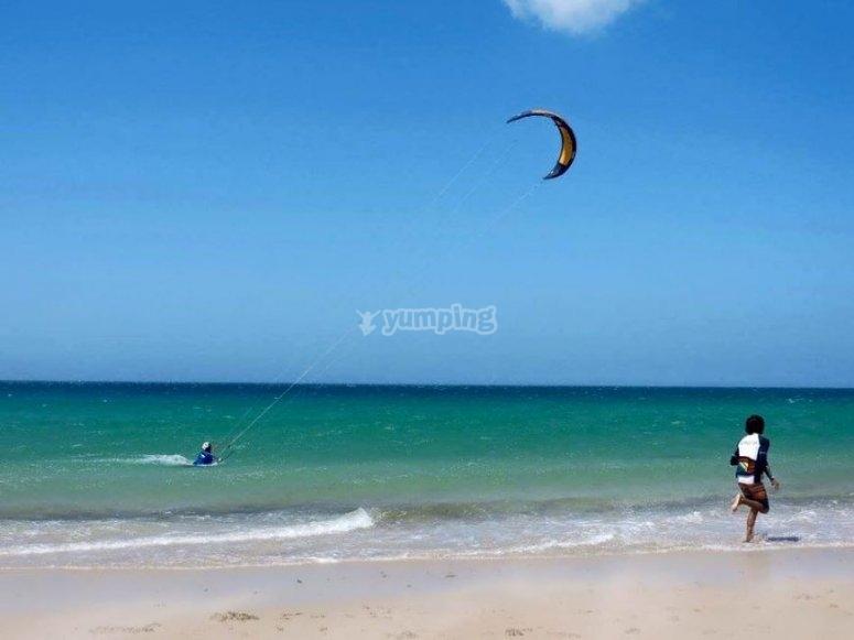 Practicando kitesurf en la playa