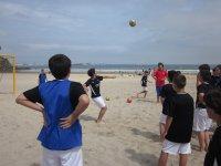 ninos jugando al futbol en la playa