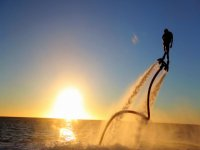 man practicing flyboard in a sunset