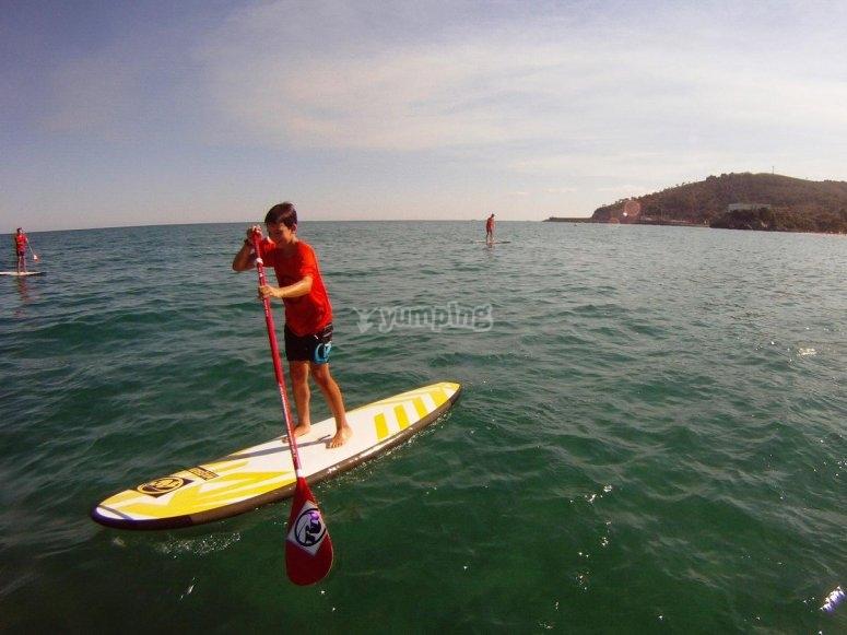 Joven aventurero haciendo paddle surf