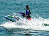 uomo con una muta che mette una moto d'acqua nel mare