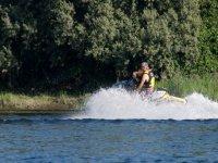 signore alla guida di un jet ski con alberi sullo sfondo