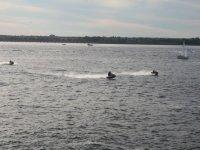 tre moto d'acqua a vela lungo una barca a vela