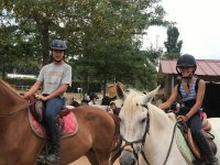 Amigas sobre los caballos en el campamento