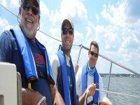 tre uomini con giubbotti di salvataggio su una barca a vela