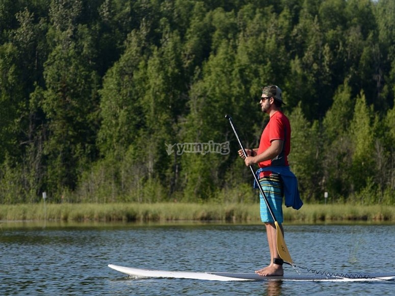Boy practicing SUP in calm waters