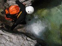 Apoyandose en la roca para bajar al rio