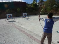 Student with the bow pointed at target