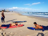 Surfers stretched on the table on the sand