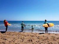 Surfistas entrando en el agua con las tablas