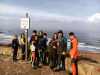 Alumnos de surf junto a la costa