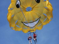 parachute of a smiling face with two people flying